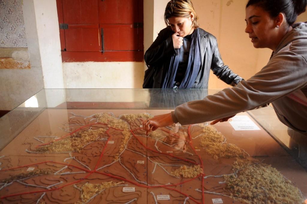 Simone explicando a maquete do assentamento Contestado; atrás, María, que veio conhecer a experiência do MST para inspirar políticas públicas de agroecologia na Venezuela.